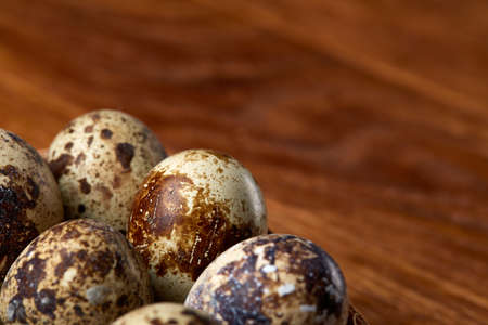 Group of three quail eggs on a wooden table, top view, close-up, selective focus, copy space. Stok Fotoğraf