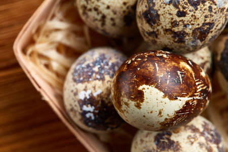 Quail eggs in a box on a rustic wooden background, top view, selective focus.