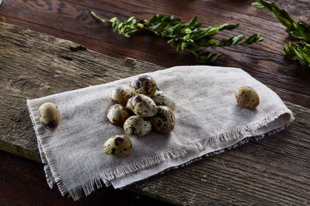 Quail eggs arranged in pyramid on a napkin with boxwood branches over a wooden table, close-up, selective focus.