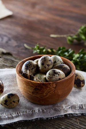 Rural still life with bowl full of eggs quail, eggs on a homespun napkin, boxwood on wooden background, top view