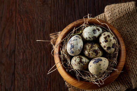 Rustic still life with quail eggs in bucket, box and bowl on a linen napkin over wooden background, selective focus
