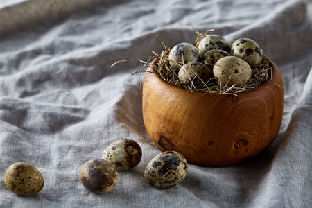 Quail eggs in a wooden bowl on a homespun tablecloth, top view, close-up Standard-Bild