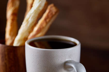 Coffee cup, breadsticks and croissants on an old wooden background, close-up, selective focus. Banque d'images