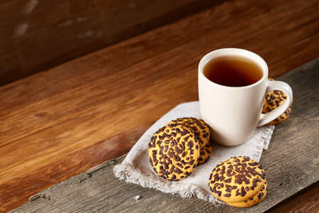 Cup of tea and chocolate chip cookies on white homespun napkin in country style on wooden table. Delicious breakfast on rustic wooden table with selective focus. Yummy snack. Sweet bakery. Food concept. Stok Fotoğraf