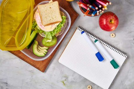 Concept of school lunch break with healthy lunch box and school supplies on white desk, selective focus, flat lay