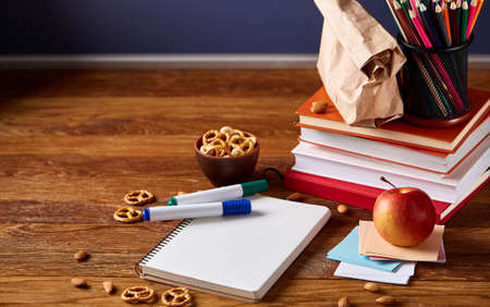 Concept of school lunch break with healthy lunch box and school supplies on wooden desk, selective focus. Stock Photo