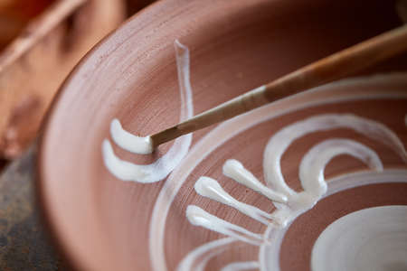 Un alfarero pinta una placa de arcilla en un blanco en el taller, vista superior, primer plano, enfoque selectivo. Foto de archivo