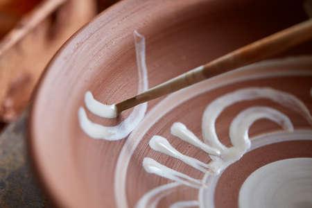 Un vasaio dipinge un piatto di argilla in un bianco in officina, vista dall'alto, primo piano, fuoco selettivo. Archivio Fotografico