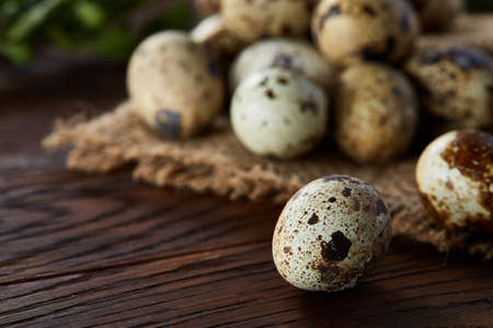 Quail eggs arranged in pyramid on a homespun napkin with some boxwood branches on a wooden table, close-up, selective focus. Conceptual Easter still life. Decorative rural composition. Healthy eating. Easter background. Healthy food concept.