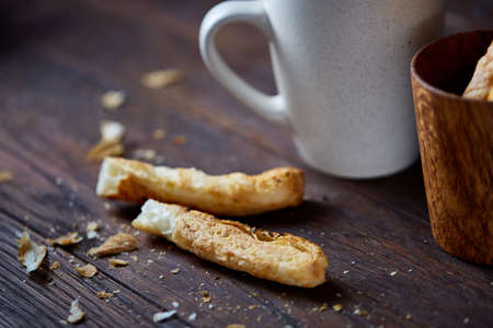 Coffee cup and breadsticks on an old wooden background, close-up, selective focus.