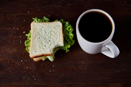 Breakfast table with fresh cheese and lettuce sandwich and black coffee in white ceramic mug on rustic wooden background, close-up, selective focus. Breakfast or lunch background. Tasty delectable appetizer. Food concept.