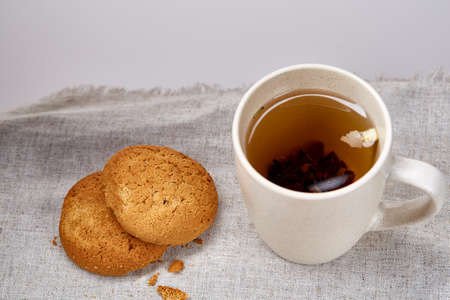 White porcelain mug of black tea or earl grey and pile of sweet cookies on homespun napkin over white background, top view, selective focus. Studio shot. Morning concept. Healthy eating concept. 写真素材