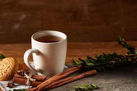 Traditional Christmas tea concept with a cup of hot tea, a large set of cookies on a homespun napkin, cinnamon sticks bunch, a couple of dried oranges and a branch of a spruce tree on a wooden table, selective focus. Festive concept.
