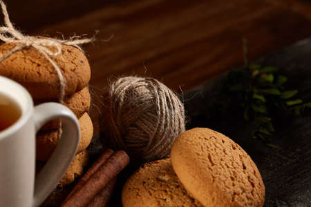 Christmas concept with a cup of hot tea, a large set of cookies on a homespun napkin, cinnamon sticks bunch, a couple of dried oranges, anise star and a branch of a spruce tree on a round log over rustic wooden background, selective focus.