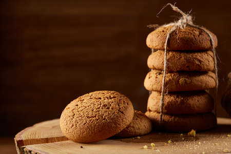 Sweet assortment of biscuits on a round wood log over rustic wooden background, close-up, selective focus. Bright gourmet sweetness. Freshly baked tasty cookies. Countryside background. Healthy eating concept. Reklamní fotografie