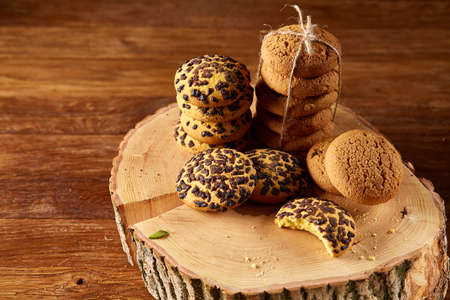 Sweet assortment of biscuits on a round wood log over rustic wooden background, close-up, selective focus. Bright gourmet sweetness. Freshly baked tasty cookies. Countryside background. Healthy eating concept. Фото со стока