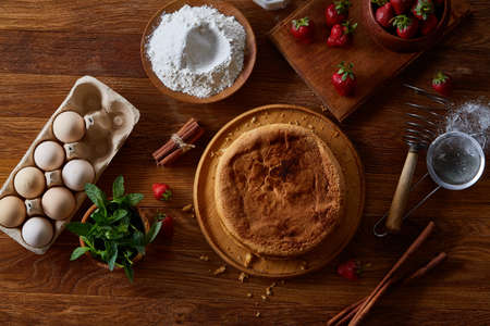 Delicious cake with fresh organic strawberries and mint, top view, close-up, selctive focus. Sweet homemade dessert surrounded by natural ingredients on wooden table. Rustic background. Tasty morning pastry. Homemade food concept. Standard-Bild - 102027682