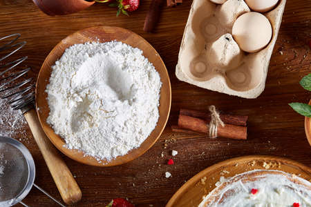 Top view raw ingredients for cooking strawberry pie or cake on wooden table: eggs, flour, milk, sugar and strawberry, flat lay. Bakery background. Recipe for strawberry pie. Tasty morning pastry. Homemade food concept. Standard-Bild