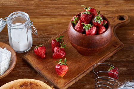 Recipe for strawberry pie, fresh strawberries, flour and sugar for cooking cake in clay bowl on wooden cutting board over rustic background, top view, selective focus. Tasty morning pastry. Homemade food concept. Bakery background.