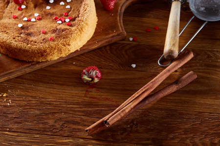 Delicious cake with fresh organic strawberries and cinnamon sticks, top view, close-up, selctive focus. Sweet homemade dessert with cinnamon on wooden table. Rustic background. Tasty morning pastry. Homemade food concept. Standard-Bild - 102026998