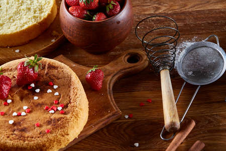 Delicious cake with fresh organic strawberries and kitchen utensils, top view, close-up, selctive focus. Sweet homemade dessert surrounded by natural ingredients on wooden table. Rustic background. Tasty morning pastry. Homemade food concept. Standard-Bild - 102027476
