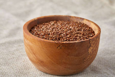 Top view close-up picture of flax seeds in wooden bowl isolated on homespun tablecloth, selective focus. Some copy space for your inscription. Nutritious and deitary ingredient. Healthy lifestyle concept.