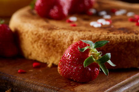 Homemade cake with fresh organic strawberries on cutting board over wooden background, close-up, selctive focus, front focus, shallow depth of field. Sweet dessert on wooden table. Rustic background. Tasty morning pastry. Food concept.
