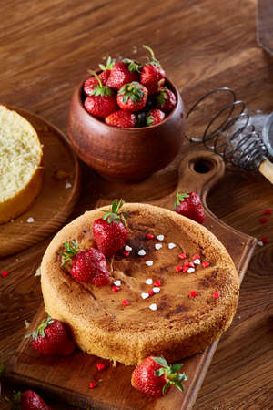 Delicious cake with fresh organic strawberries and kitchen utensils, top view, close-up, selctive focus. Sweet homemade dessert surrounded by natural ingredients on wooden table. Rustic background. Tasty morning pastry. Homemade food concept. Standard-Bild - 102027465