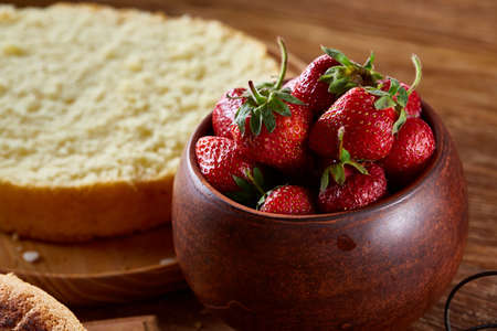 Fresh strawberries for cooking cake in wooden bowl over rustic background, top view, selective focus. Tasty morning pastry. Homemade food concept. Nesessary baking ingredientd. Bakery background.
