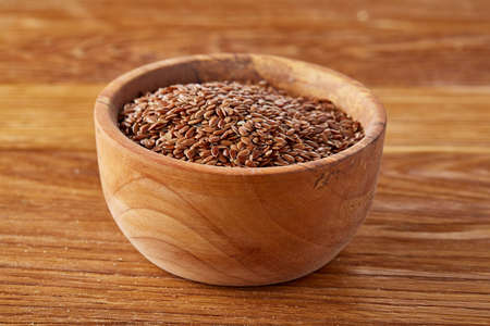 Top view close-up picture of flax seeds in wooden bowl isolated on brown rustic wooden background, shallow depth of field. Some copy space for your inscription. Nutritious and deitary ingredient. Healthy lifestyle concept. Imagens