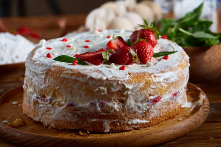 Strawberry tart covered with whipped sour cream on a wooden tray over rustic background, close-up, selective focus, shallow depth of field. Homemade bakery with fresh eggs, mint leaves, organic strawberry and flour. Food concept. Bakery background. Stock Photo