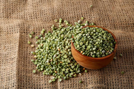 Organic green peas in a bowl and some beans on burlap tablecloth, close-up, top view, selective focus. Studio shot. Nutritious organic protein. Healthy food concept. Healthy eating, dieting. Stock fotó