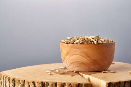 Close-up oat groats heaped in a wooden bowl on a wooden log over grey studio background, selective focus. Some copy space for your text. Healthy eating, dieting. Natural nutritious oatmeal. Vegan cuisine. Organic food concept. Foto de archivo