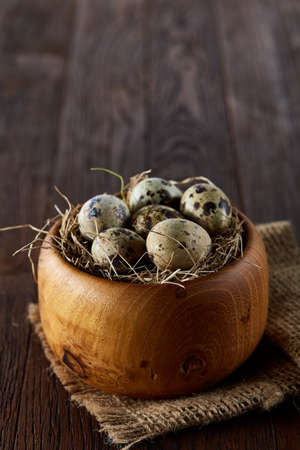 Fresh quail eggs in a wooden bowl on a homespun napkin over dark wooden background, top view, close-up.