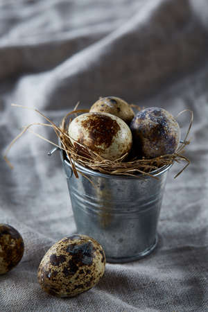 Fresh spotted quail eggs in a decorative metal bucket and some eggs on a homespun tablecloth, top view, close-up, vertical. Some copy space for your inscription. Studio shot. Traditional poultry. Healthy eating. Healthy lifestyle concept. 스톡 콘텐츠