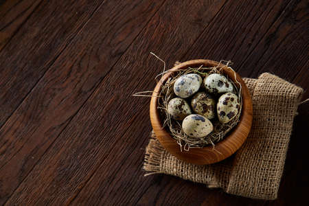 Rural still life with wooden bowl full of quail eggs, eggs on a homespun napkin and boxwood branches over wooden background, close-up, selective focus, top view. Conceptual Easter still life. Decorative composition. Healthy food concept.