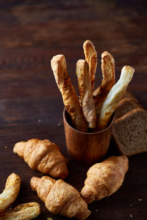 Puff pastries on dark wooden table, close-up, selective focus, backlight. Delicious freshly baked breadsticks and homemade croissats on rustic background. Yummy sweetbread. Rural still life. Food concept. Breakfast background. Stock Photo