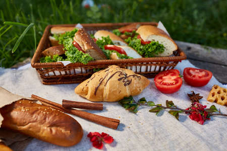 Picnic basket full with sandwiches, baguette and croissant on a homespun tablecloth, summer season, flat lay, selective focus. Fresh croissants, baguette, tomatoes and vegetarian sandwiches artistically arranged on wooden table. Leasure summer snack.