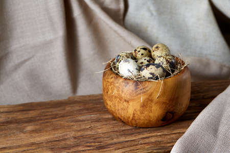 Fresh spotted quail eggs in a wooden bowl on a homespun tablecloth, top view, close-up, blurred. Some copy space for your inscription. Studio shot. Traditional poultry. Healthy eating. Healthy lifestyle concept.