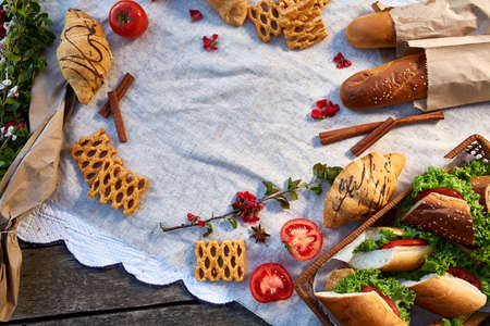 Picnic on a green lawn, pastries and vegetables on a homespun tablecloth, summer season, flat lay, selective focus. Fresh croissants, baguette, biscuits and vegetarian sandwiches artistically arranged on wooden table. Leasure summer snack.