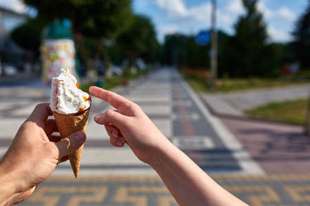 A first person view, sweethearts walking along the road, holding ice cream in their hands and eating it on the colorful pavement background, shallow depth of field. Vanilla ice-cream is the most romantic snack. Sweet refreshing summer food concept.