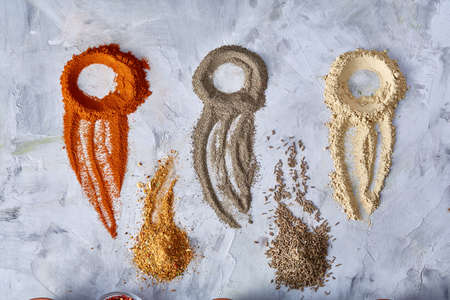 Creative food art concept with abstract figures made of ground spicies on white textured background, top view, close-up, selective focus. Some copy space for your inscription or text. Healthy meal. Organic condiment. Food art concept.