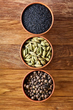 Three bowls with assortment of spicy arranged in row on wooden table, top view, close-up, selective focus, vertical. Pimento, black sesam, cardamon, on rustic wooden background. Aromatic flavouring. Healthy eating and dieting concept.