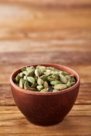 Green cardamon in ceramic bowl on rustic wooden background close-up, top view, selective focus, vertical. Some copy space for your text. Exotic indian spice. Aromatic condiment. Healthy eating and dieting concept. Stock Photo