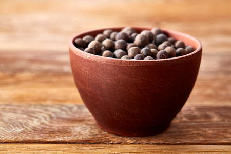 Close-up of clay bowl with dried allspice berries on vintage wooden background, side view, macro, shallow depth of field. Some copy space for your text. Exotic asian spice. Piquant flavour. Aromatic condiment. Healthy eating and dieting concept.