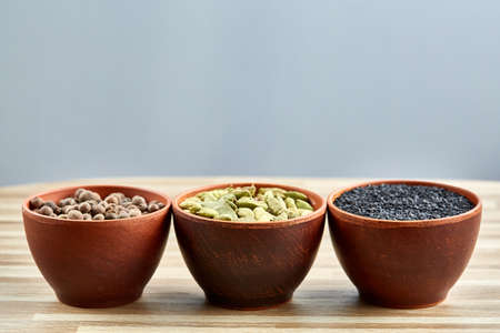Three bowls with assortment of spicy arranged in row on kitchen table, top view, close-up, selective focus, vertical. Pimento, black sesam, cardamon, on rustic wooden background. Aromatic flavouring. Healthy eating and dieting concept.