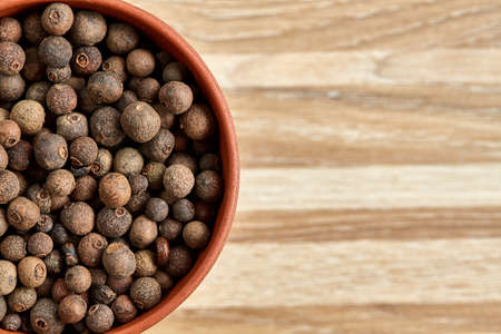 Close-up half view of clay bowl with dried allspice berries on textured wooden background, macro, selective focus. Some copy space for your text. Exotic asian spice. Piquant flavour. Aromatic condiment. Healthy eating and dieting concept.