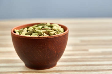 Green cardamon in ceramic bowl on wooden table close-up, top view, selective focus. Some copy space for your text. Exotic indian spice. Aromatic condiment. Healthy eating and dieting concept.