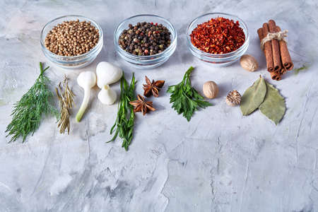 Three glass bowls with spices arranged in rows on white textured background, view from above, selective focus. Some copy space for your text. Bowls with chilly, peppercorns, coriander togather with cinnamon, bay leaf, parsley, nutmeg, dill, rosemary. Stockfoto