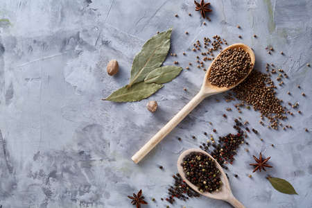 Composition of assortment of spices in the wooden spoons cinnamon sticks bunch and dried bayleaf on the white background, flat lay, close-up, selective focus. Aromatic peppercorn and mustard seeds. Food background. Stock Photo